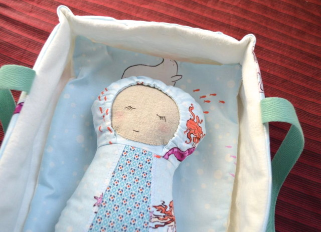 baby doll in carrier with mattress and blanket